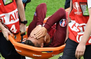 Portugal's forward Cristiano Ronaldo reacts as he is carried on a stretcher off the pitch by team medics after an injury following a clash with France's forward Dimitri Payet (not pictured) during the Euro 2016 final football match between Portugal and France at the Stade de France in Saint-Denis, north of Paris, on July 10, 2016. / AFP PHOTO / PHILIPPE LOPEZPHILIPPE LOPEZ/AFP/Getty Images ORIG FILE ID: 553892848